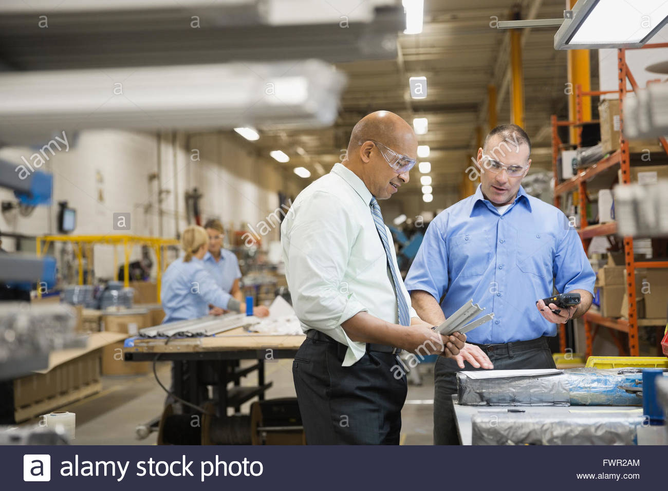 Manager and worker looking at metal parts - Stock Image