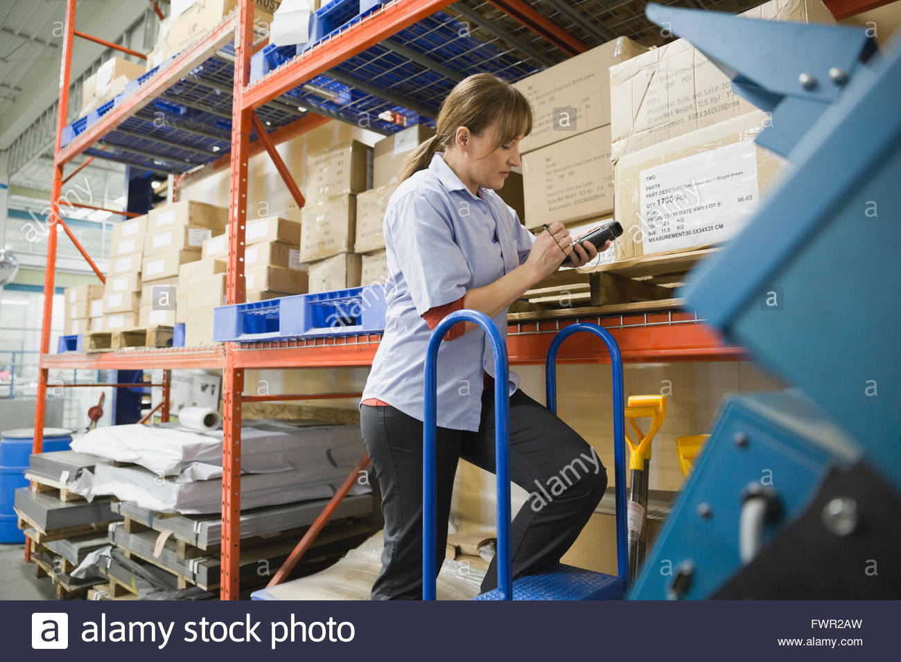 Worker using bar code reader in warehouse - Stock Image