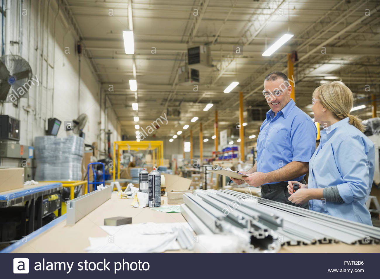 Manual workers in metal factory - Stock Image