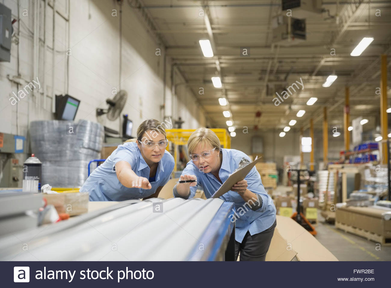 Female workers analyzing metal products in warehouse - Stock Image