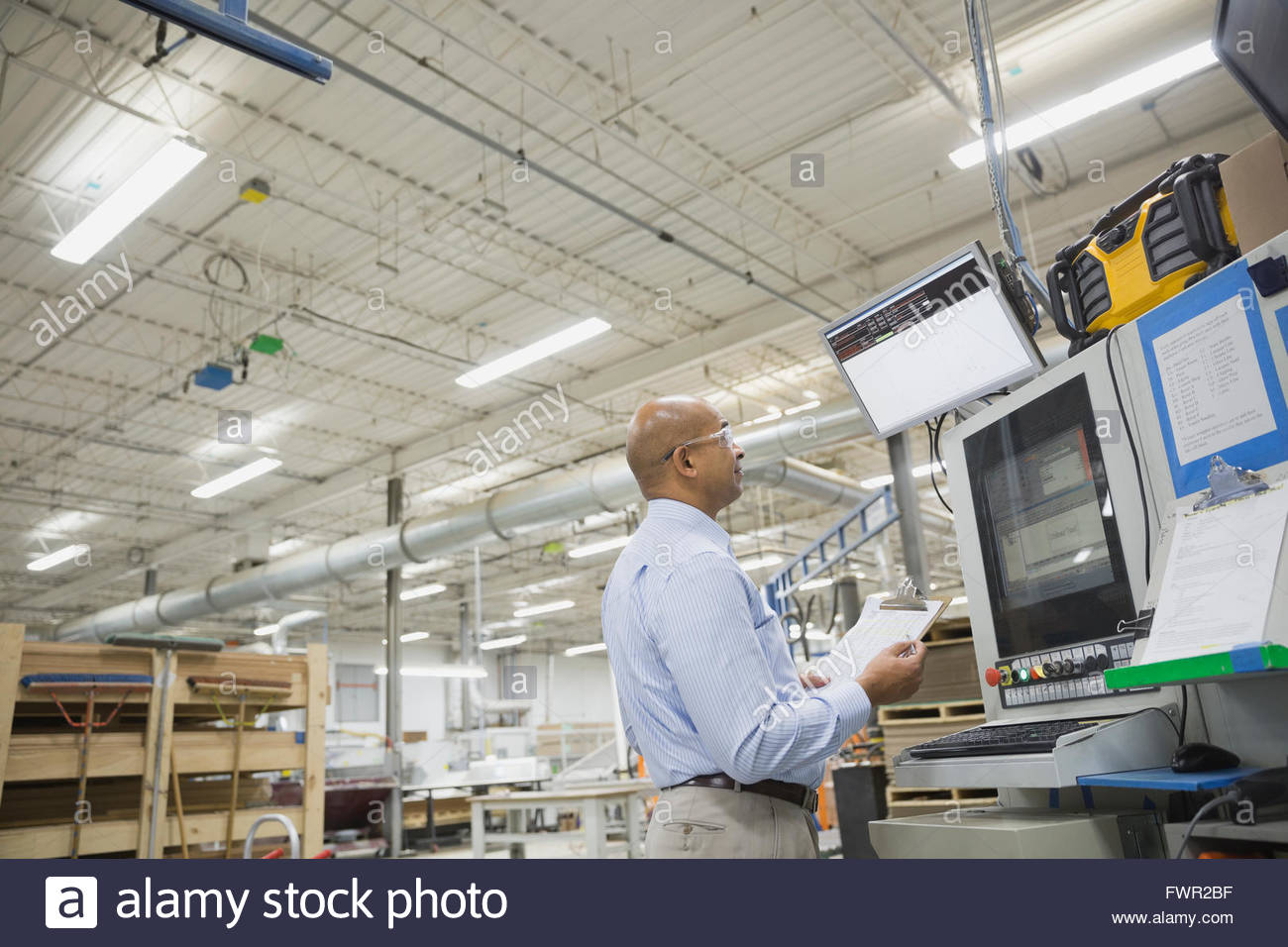 Manager looking at computer monitor in factory - Stock Image