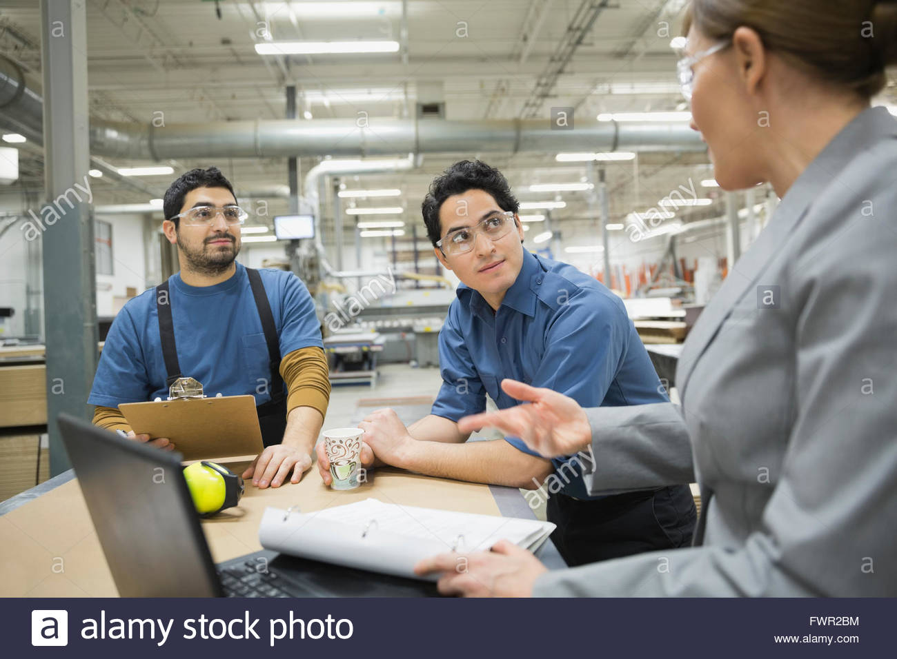 Manager and manual workers talking in factory - Stock Image