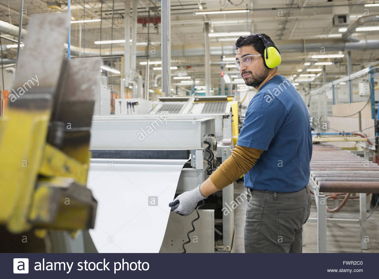 Worker extracting steel sheet from machine in factory - Stock Image
