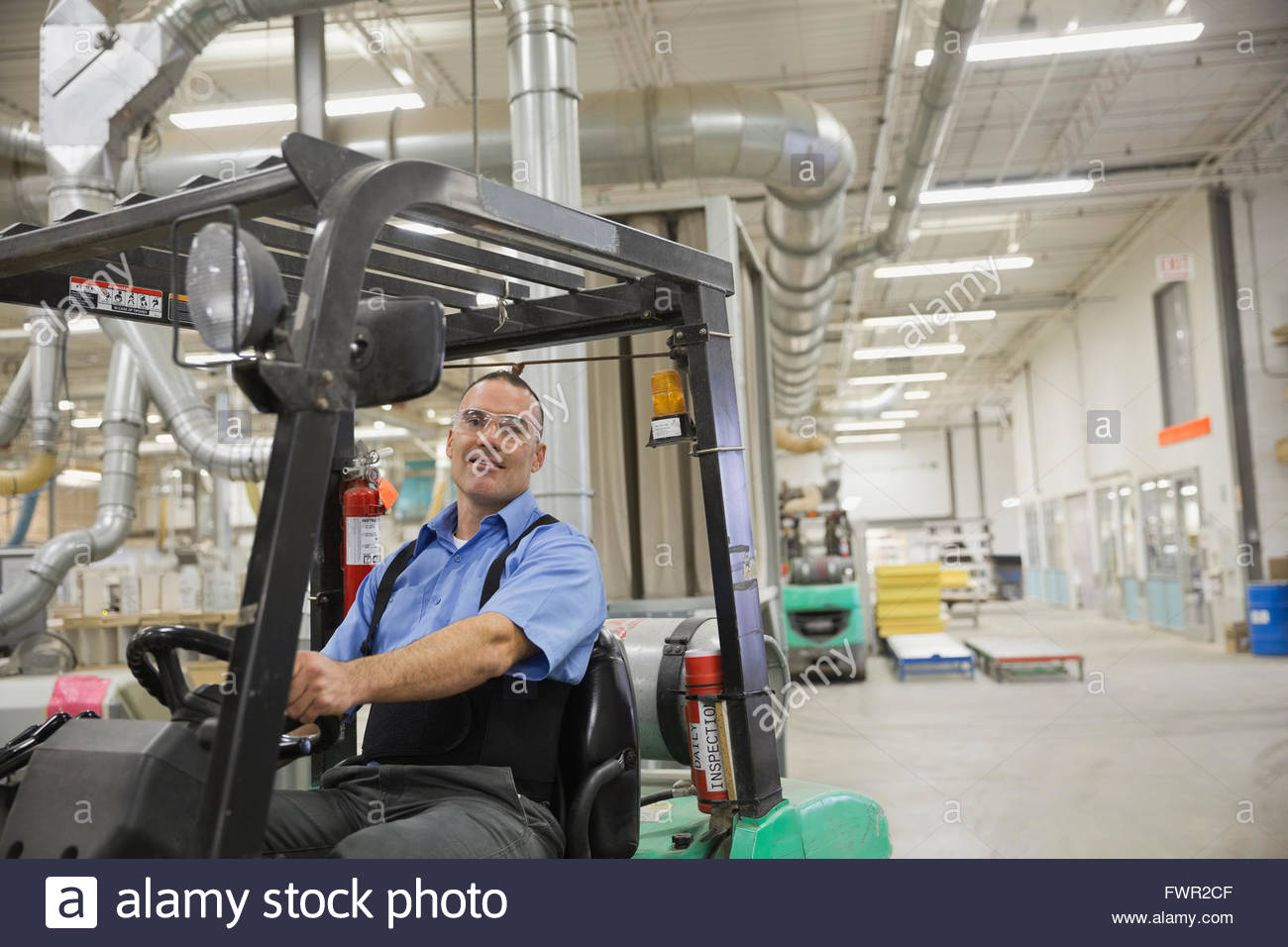 Manual worker driving forklift in factory - Stock Image