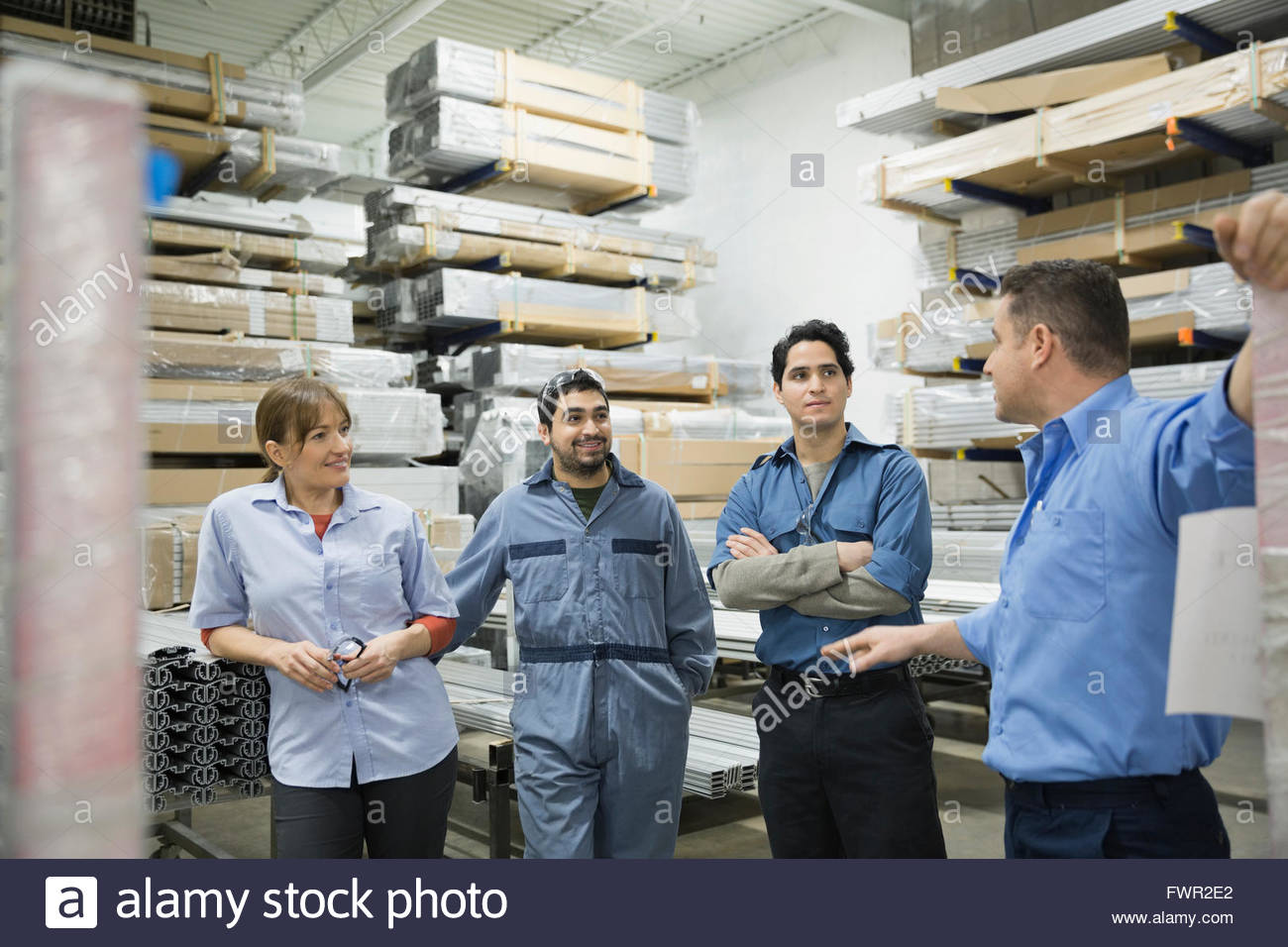 Manual workers meeting in warehouse - Stock Image