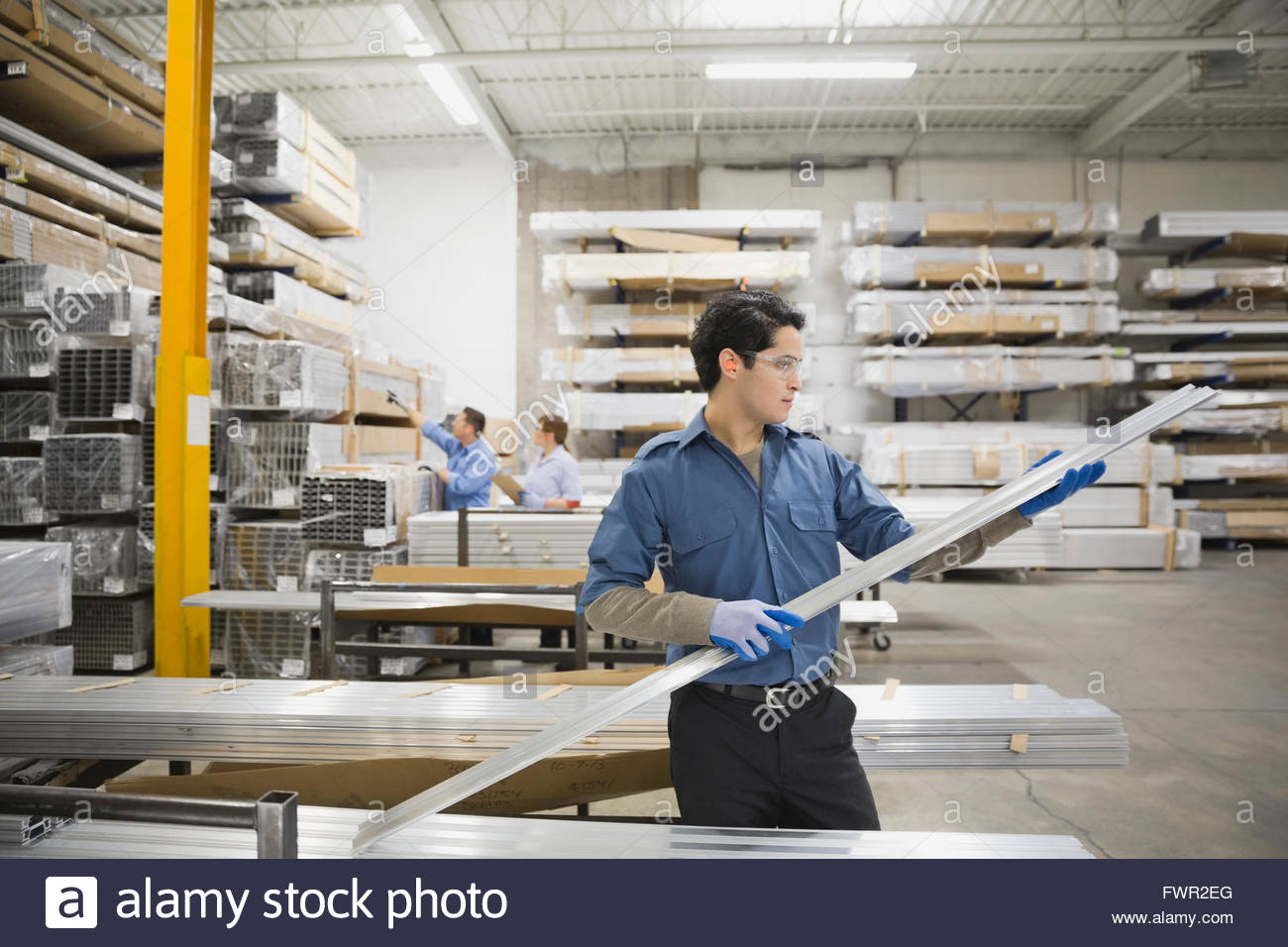 Worker examining steel parts in factory - Stock Image