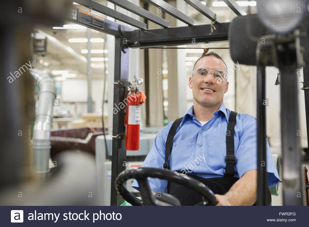 Portrait of worker sitting in forklift - Stock Image