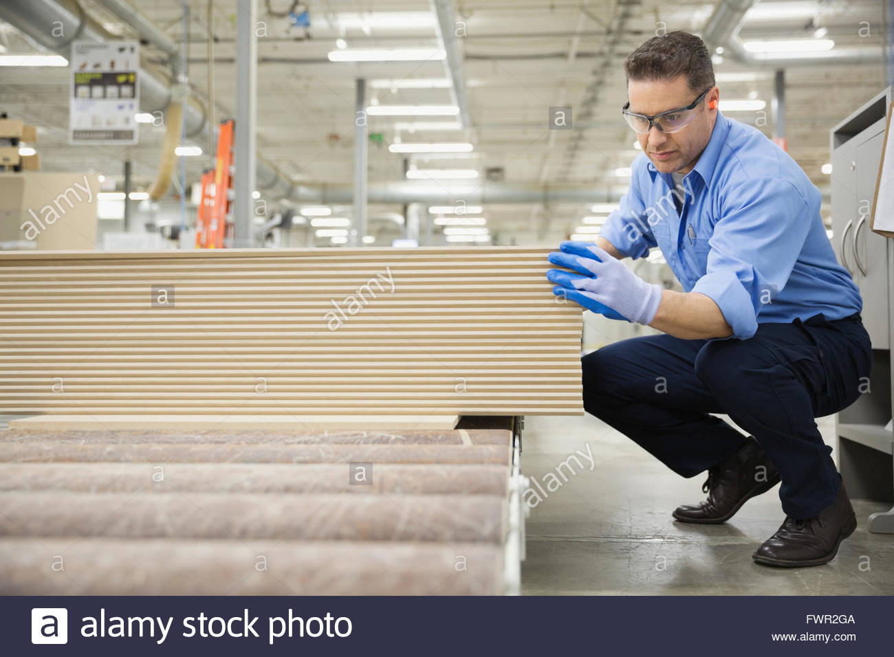 Worker examining wooden planks in factory - Stock Image