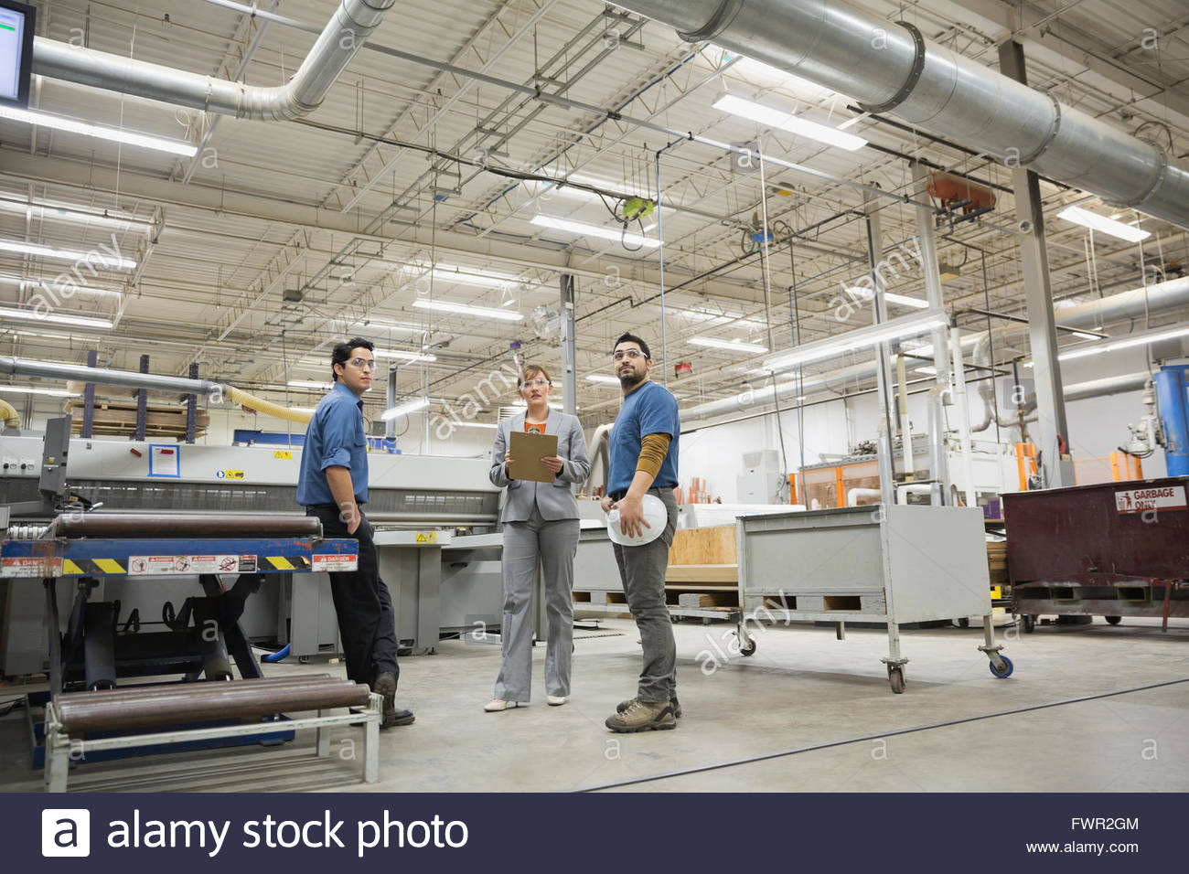 Manager and manual workers in factory Stock Photo