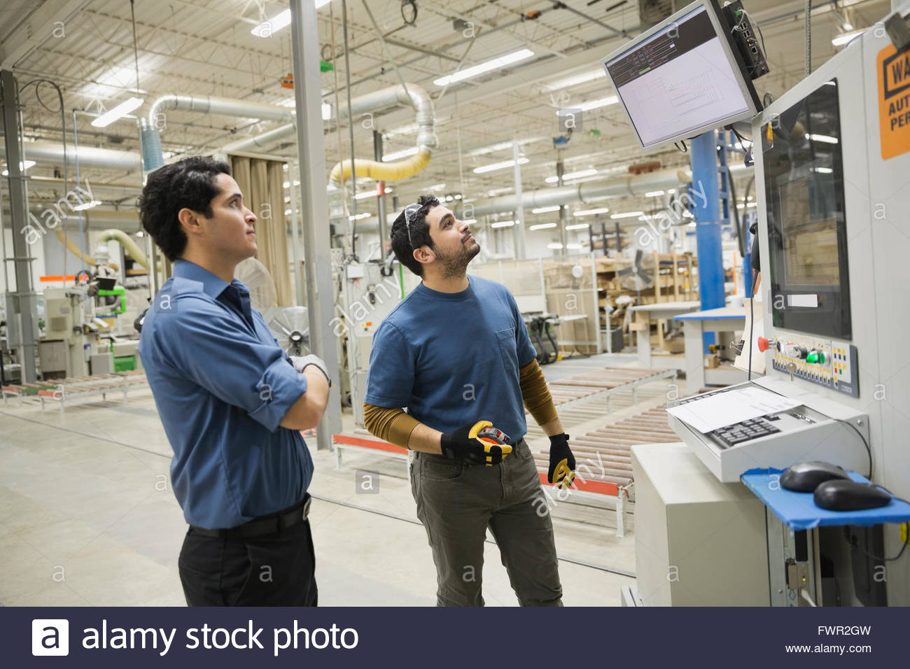 Manual workers looking at screen in warehouse - Stock Image