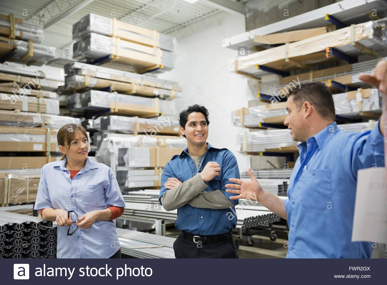 Worker explaining to colleagues in warehouse - Stock Image