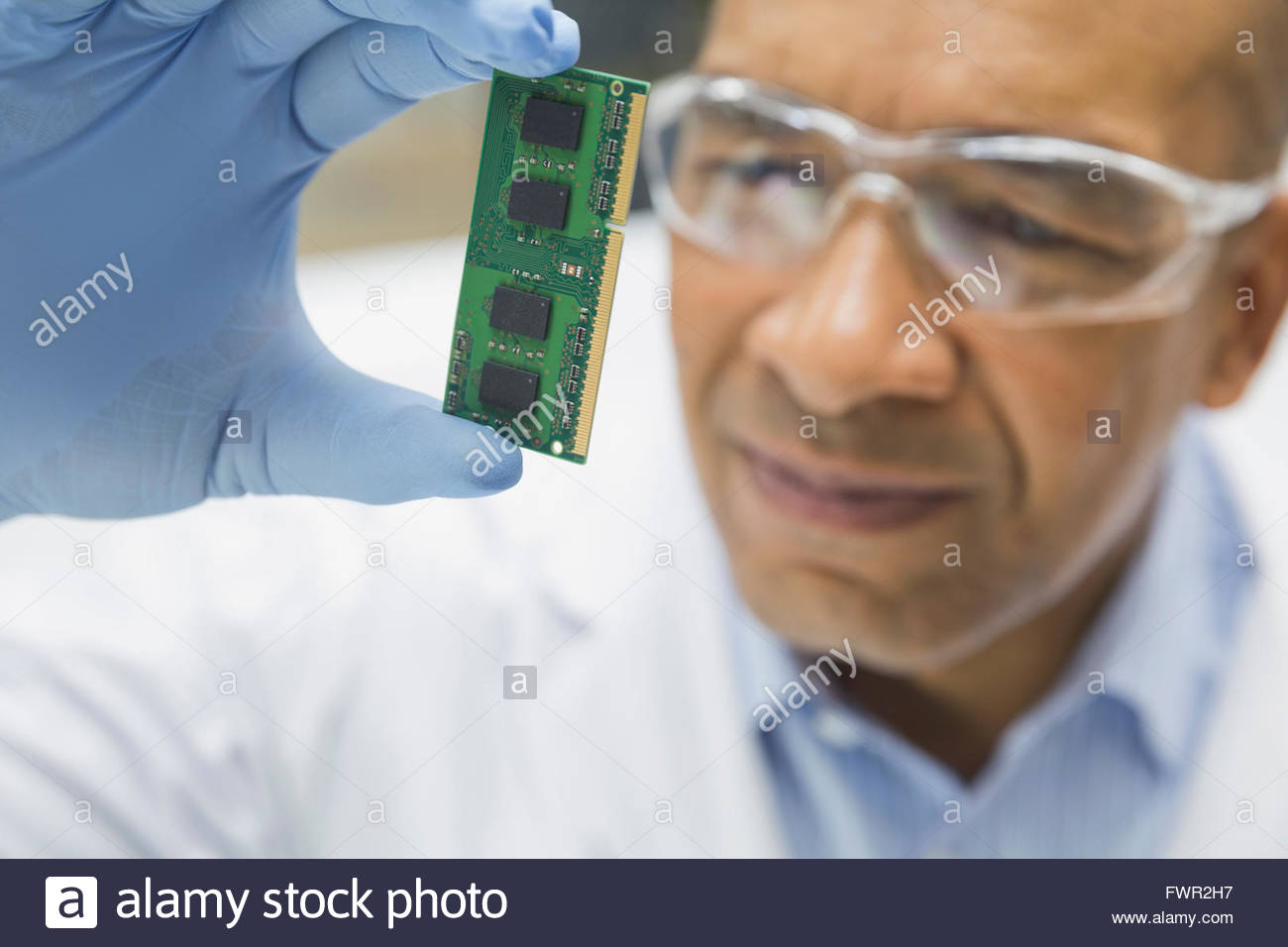 Technician examining computer chip - Stock Image