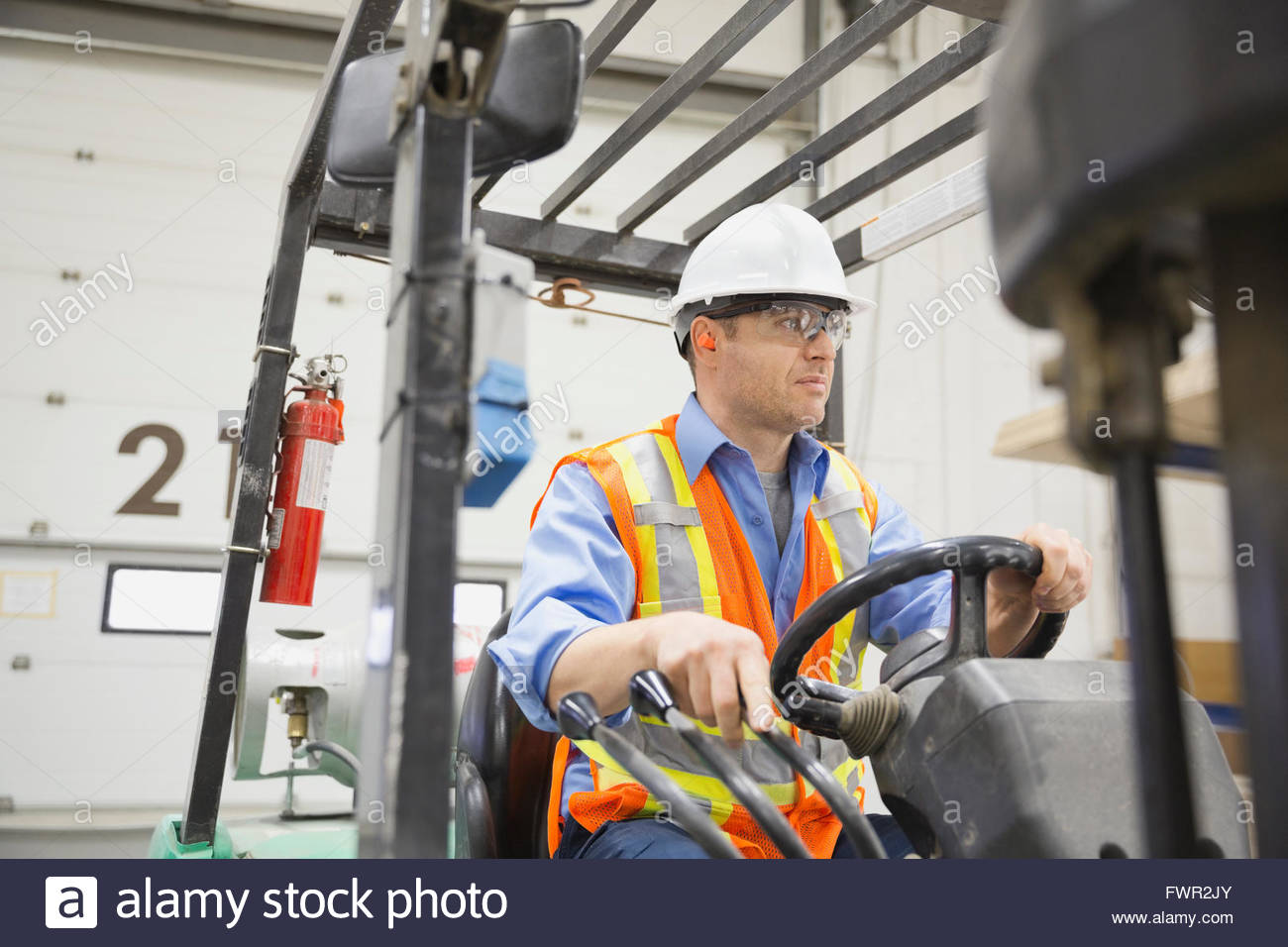 Manual worker driving forklift in warehouse - Stock Image