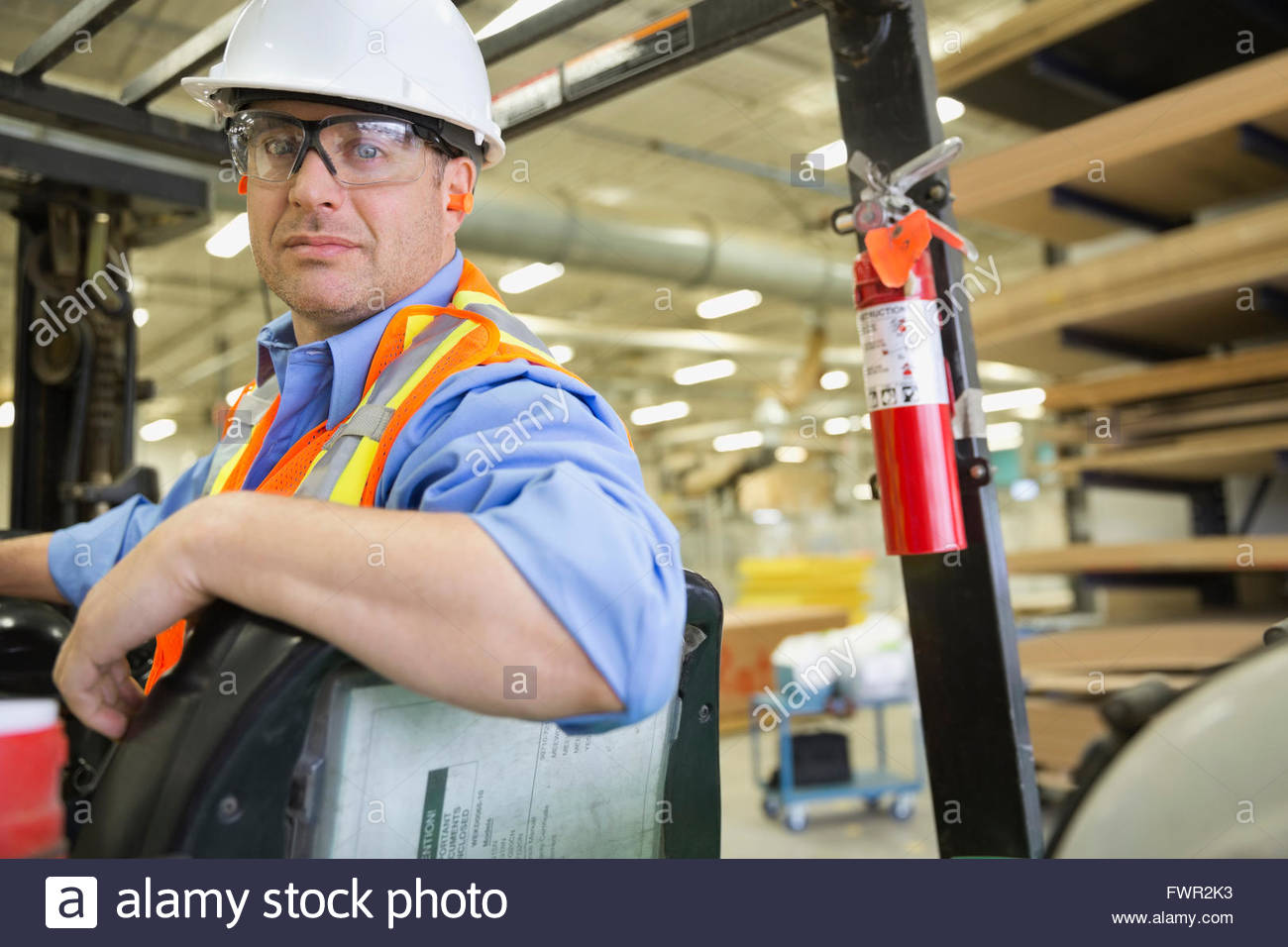 Manual worker driving forklift in industry - Stock Image
