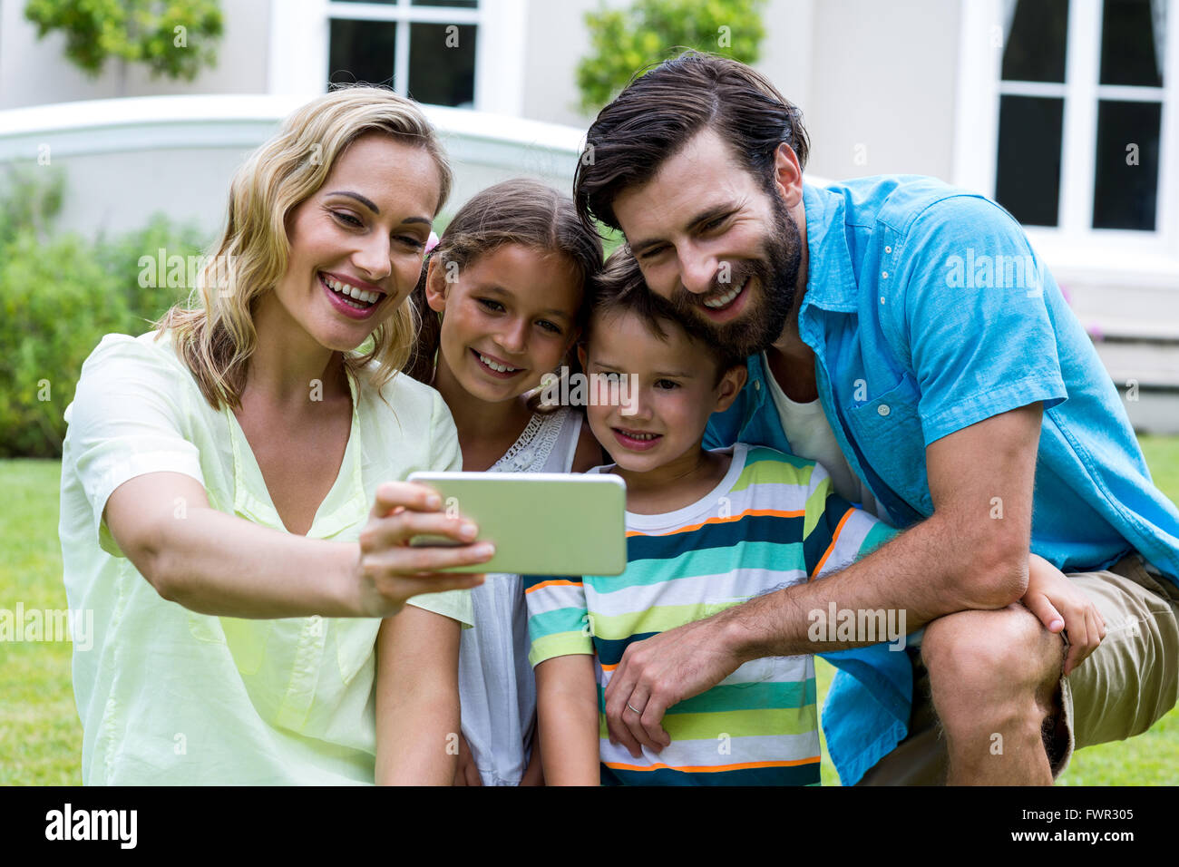 Mother taking selfie with family in yard - Stock Image