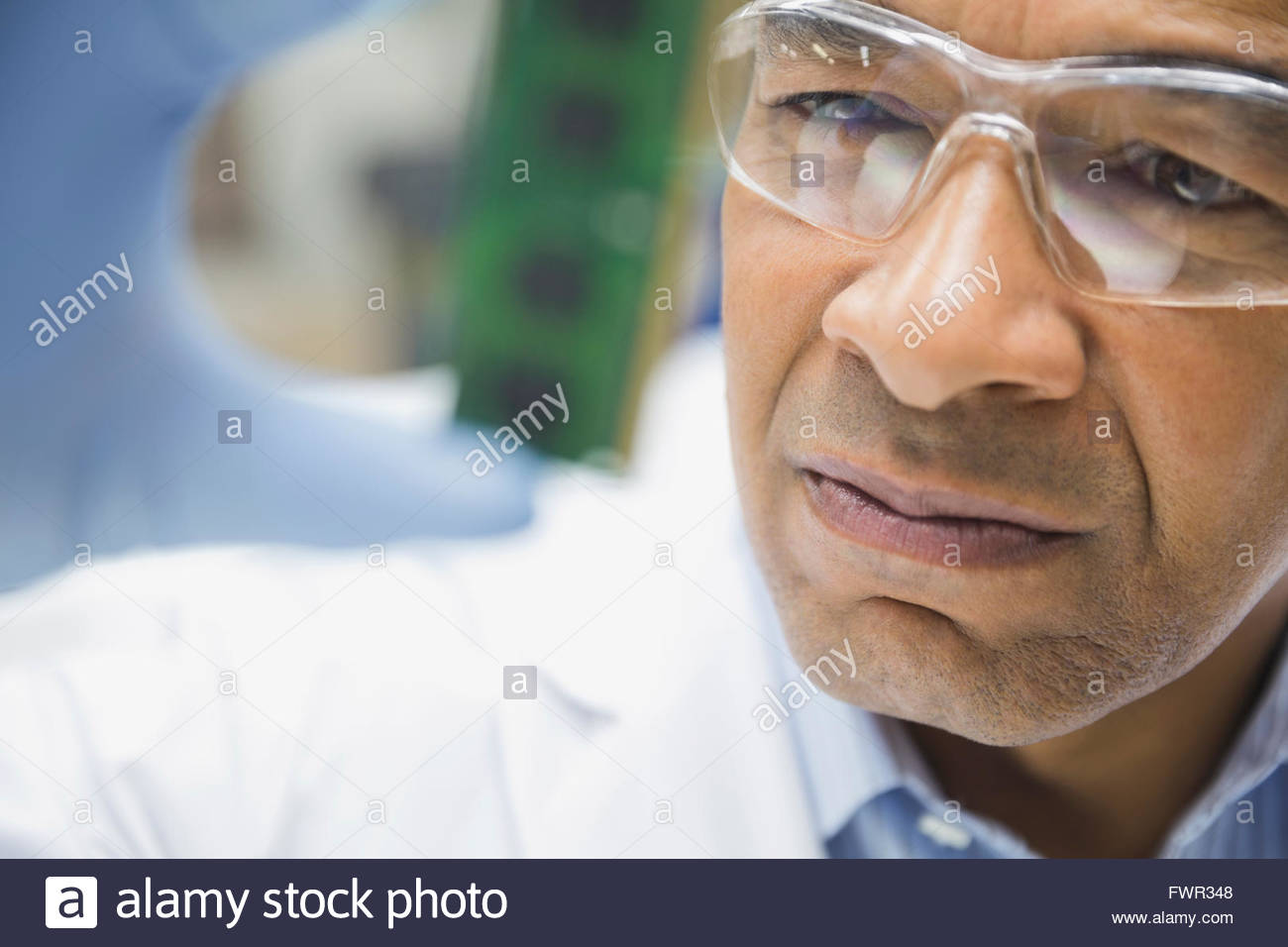 Technician looking at computer chip - Stock Image