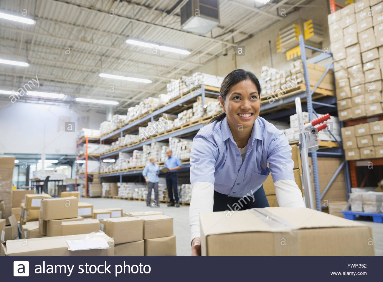 Female worker with boxes in warehouse - Stock Image