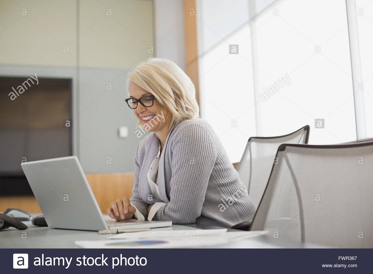 Businesswoman using laptop in boardroom - Stock Image