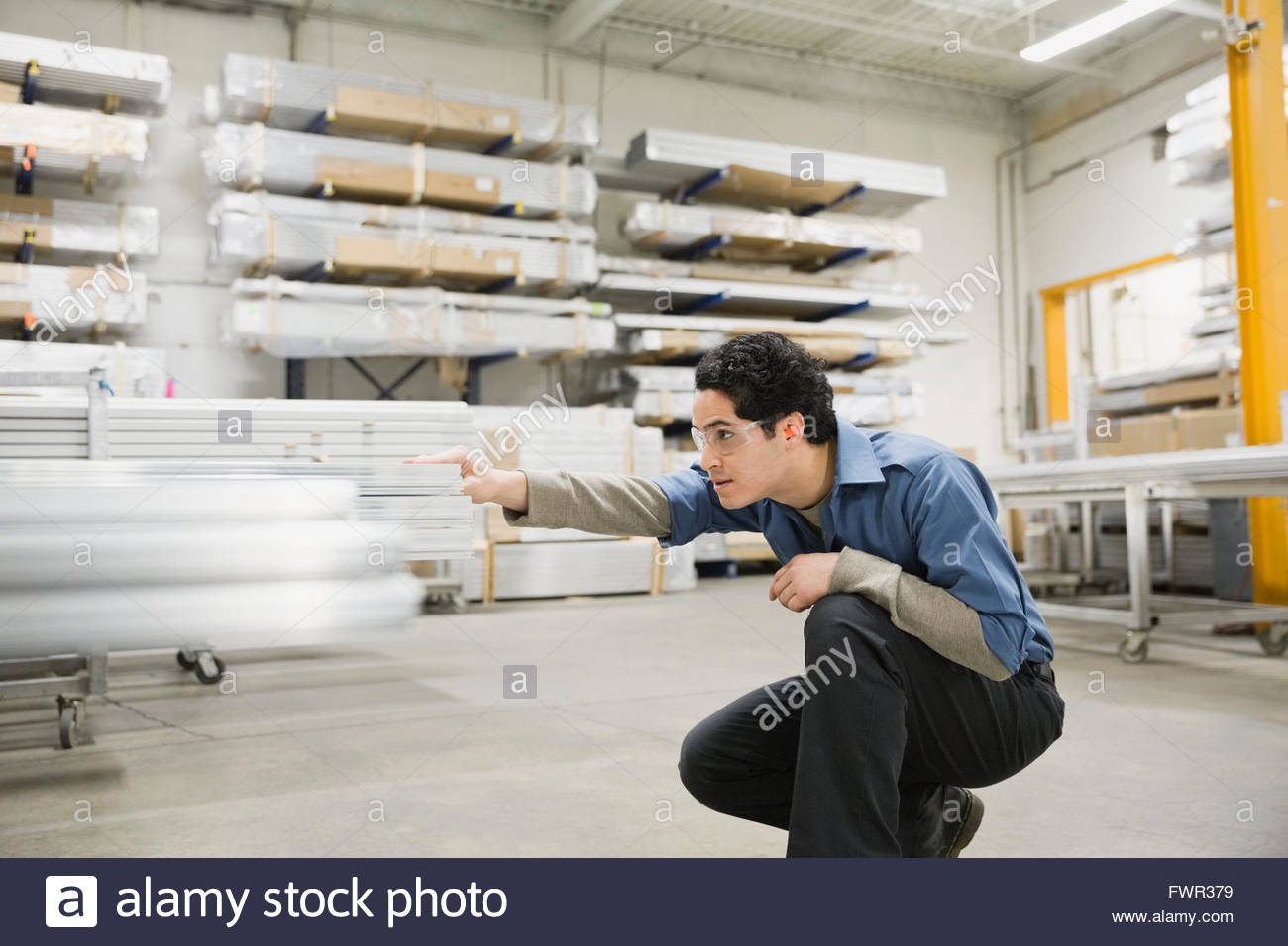 Worker examining metal in warehouse Stock Photo