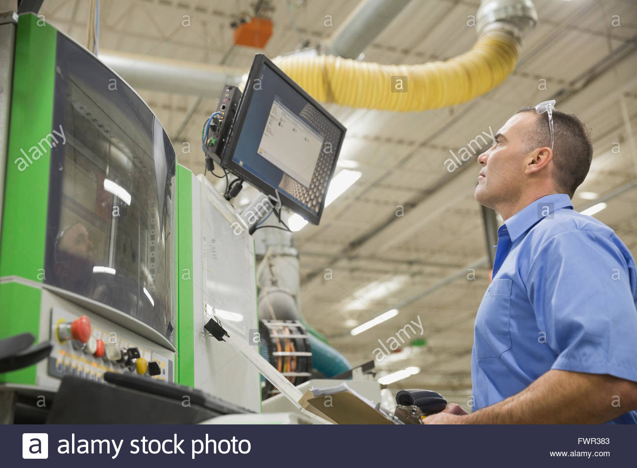 Worker looking at computer monitor in factory - Stock Image