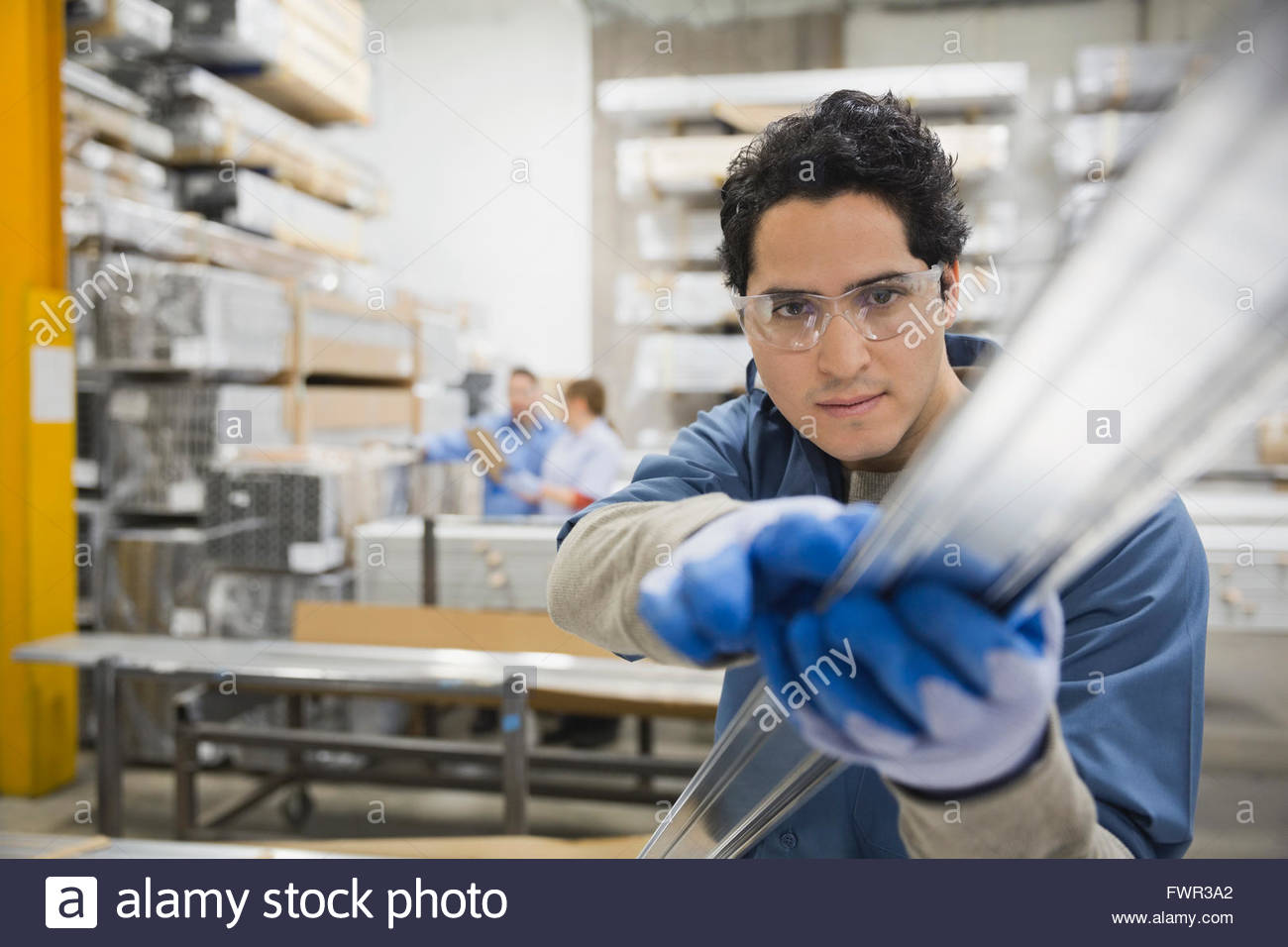 Male worker examining metal in warehouse - Stock Image