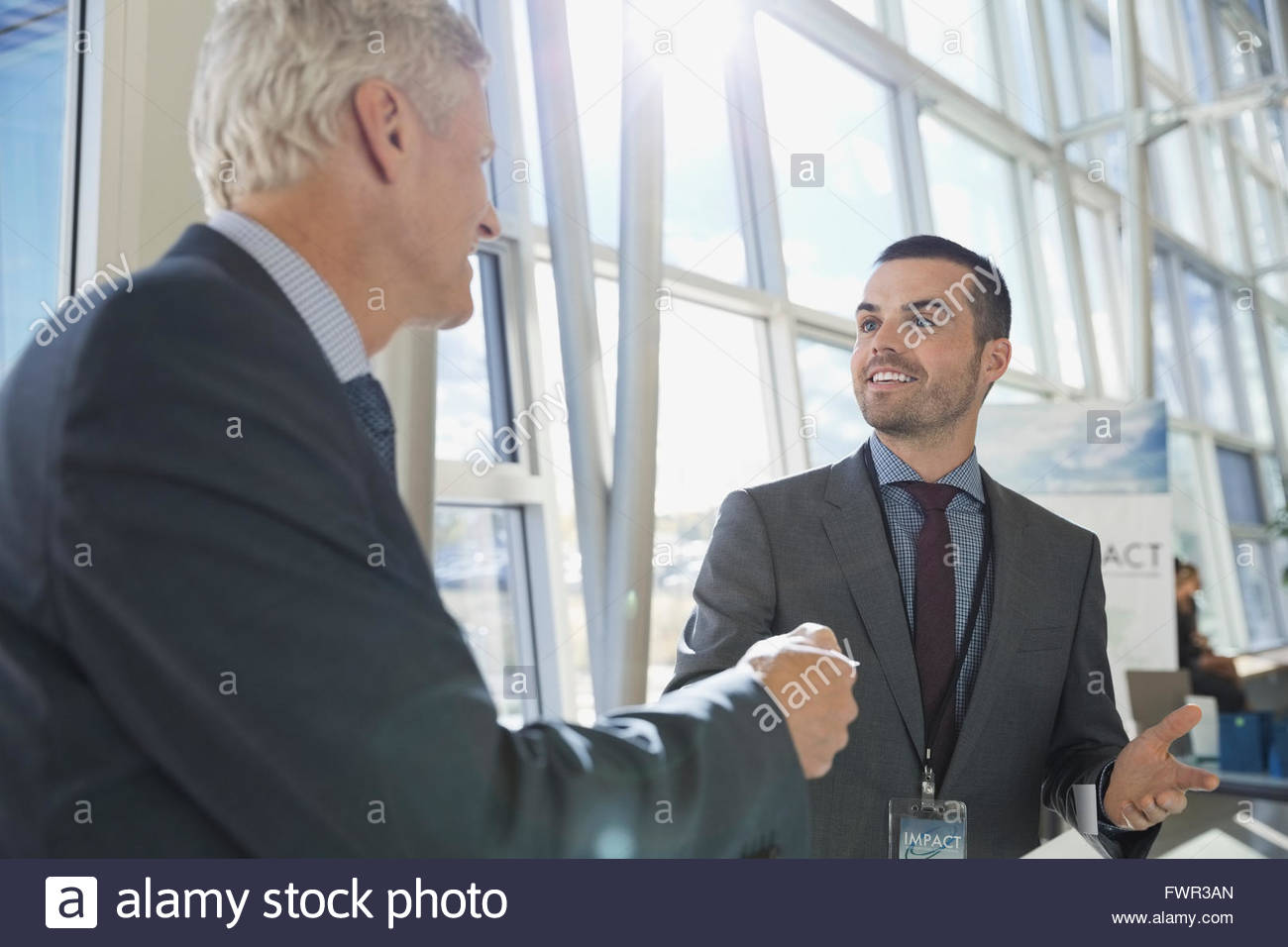 Businessmen exchanging business cards - Stock Image