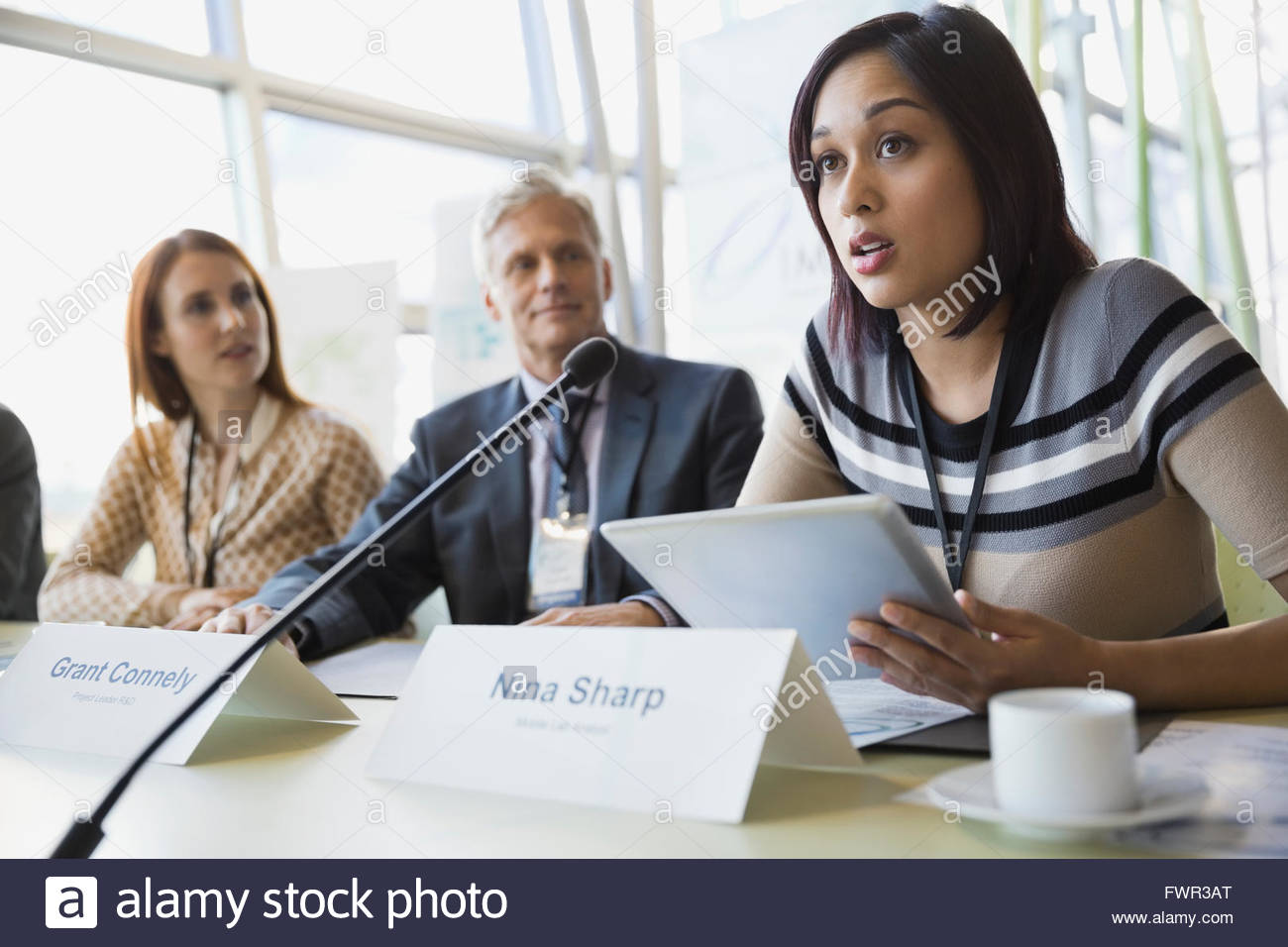 Businesswoman using digital tablet while leading conference talks - Stock Image