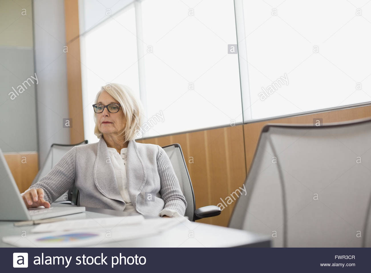 Businesswoman working on laptop in boardroom - Stock Image