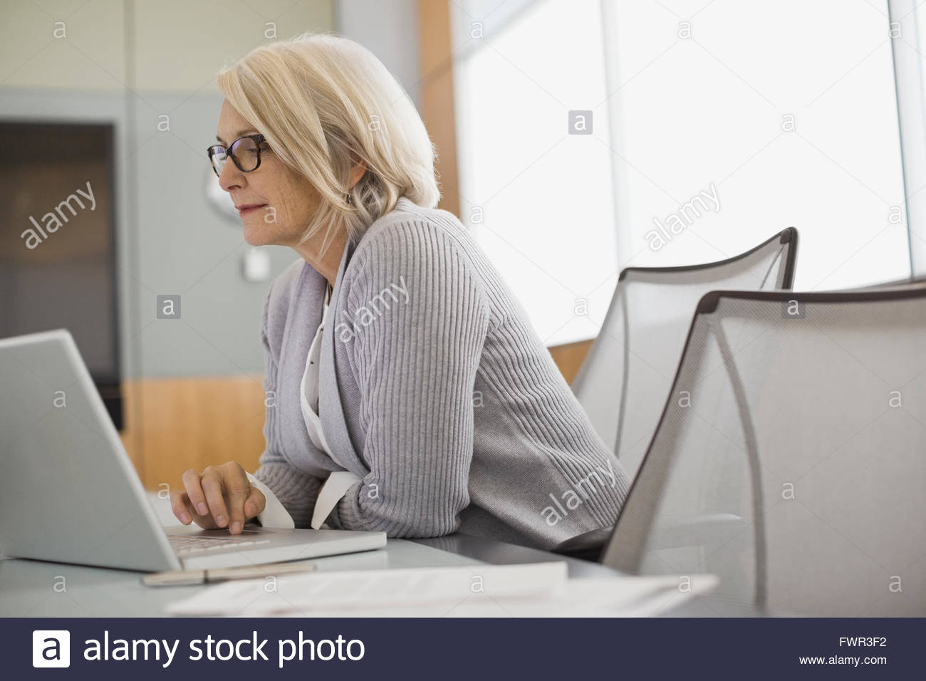 Businesswoman using laptop at conference table - Stock Image