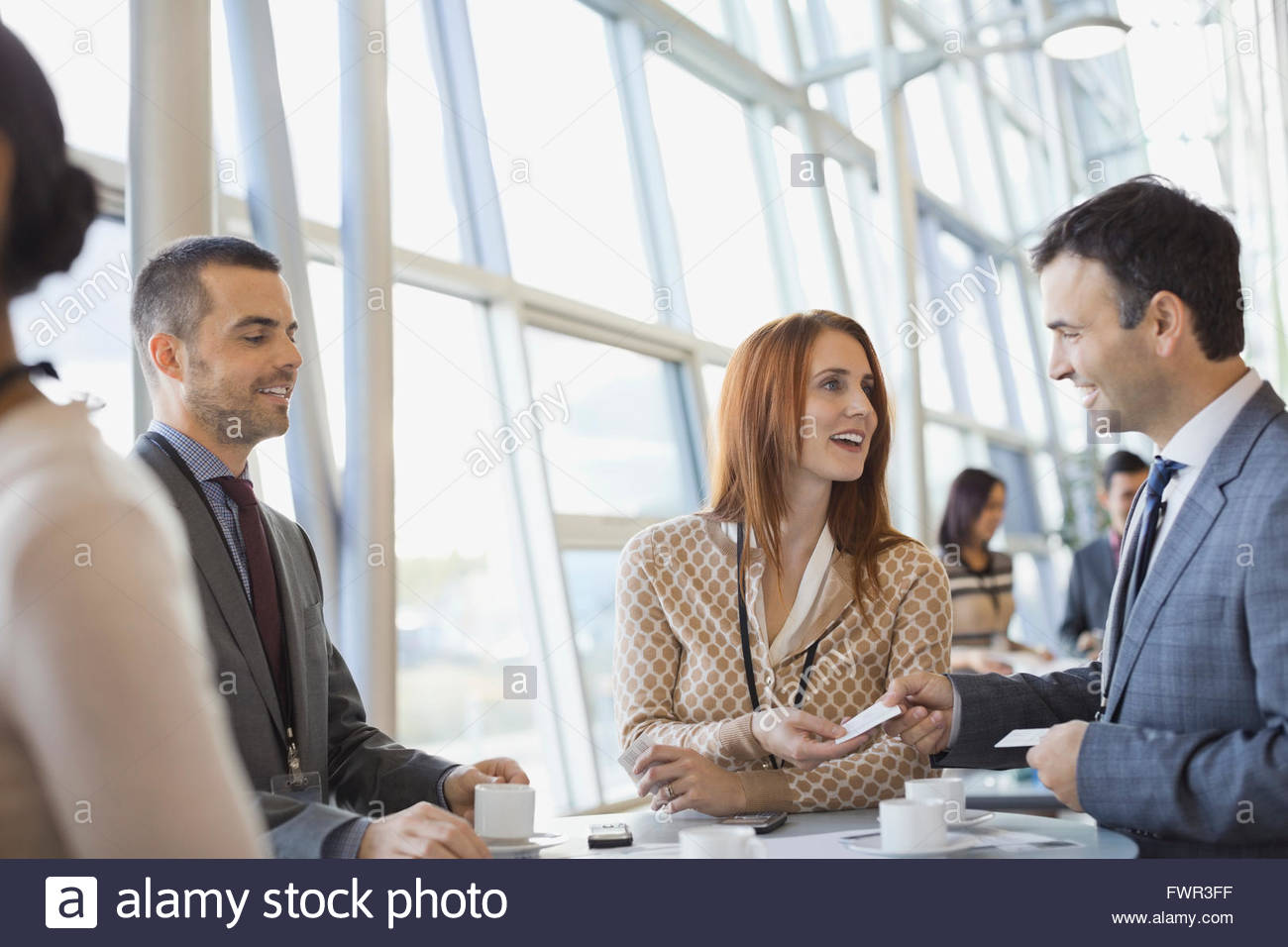 Business people exchanging business cards at conference - Stock Image