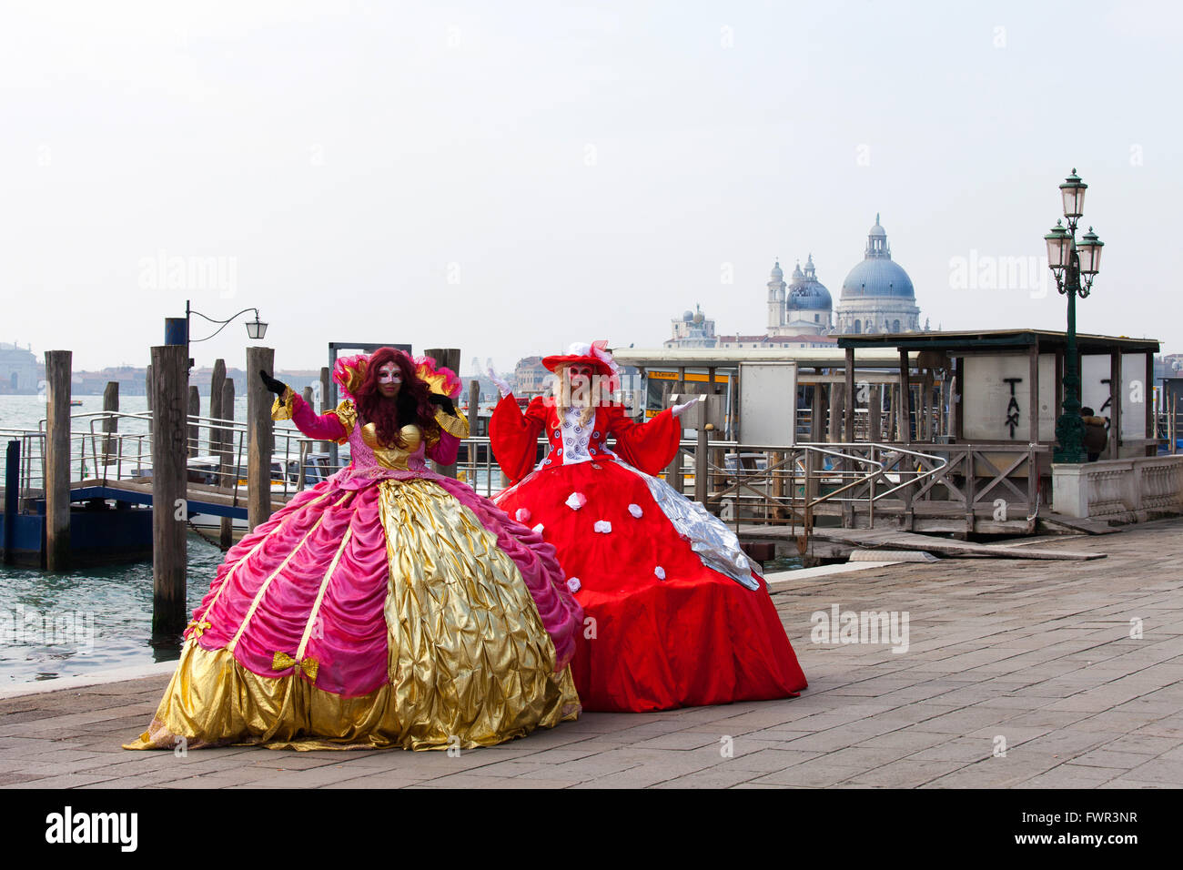 Two ladies in a traditional Venetian carnival dress and masks, at Piazza San Marco. Stock Photo