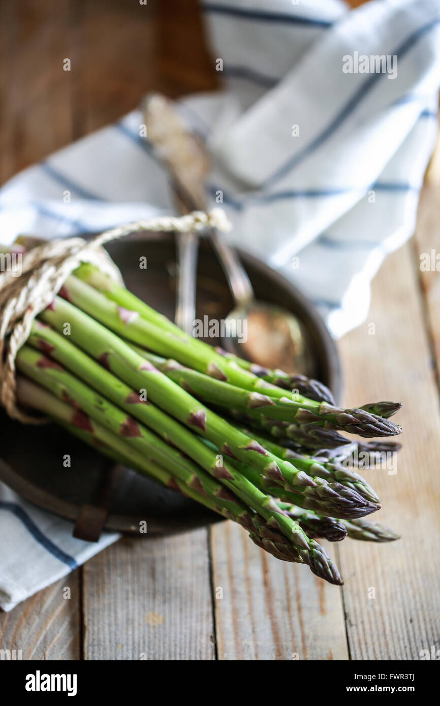 Bunch of fresh asparagus on wooden table - Stock Image