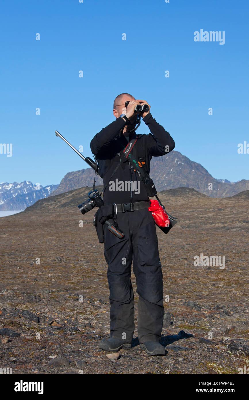 Polar bear guard armed with rifle looking for polar bears through binoculars, Svalbard, Norway - Stock Image
