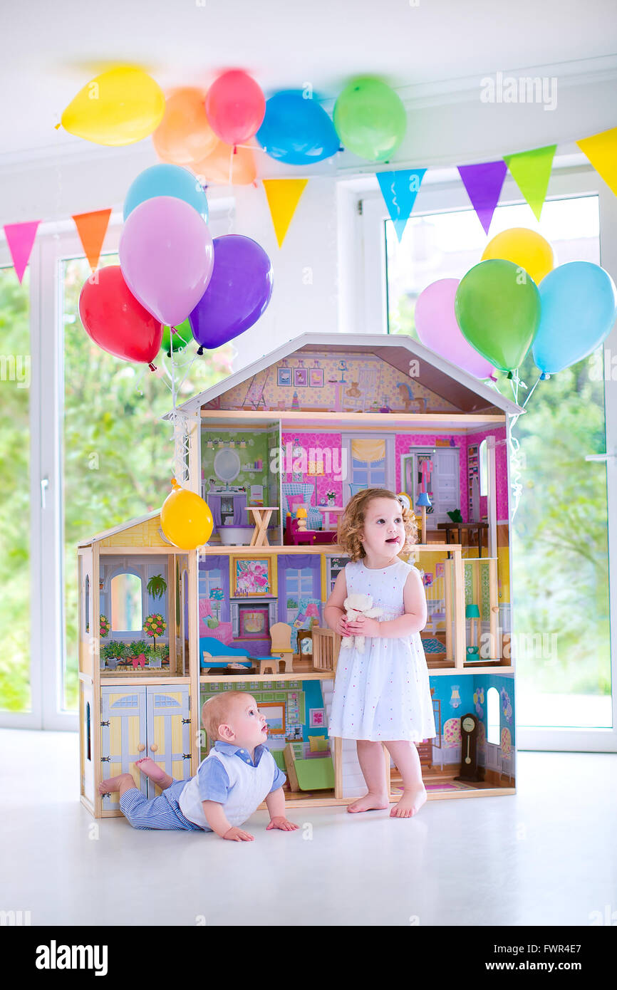 Adorable Curly Toddler Girl In White Dress And Her Little Baby Brother Playing Together With Birthday Present