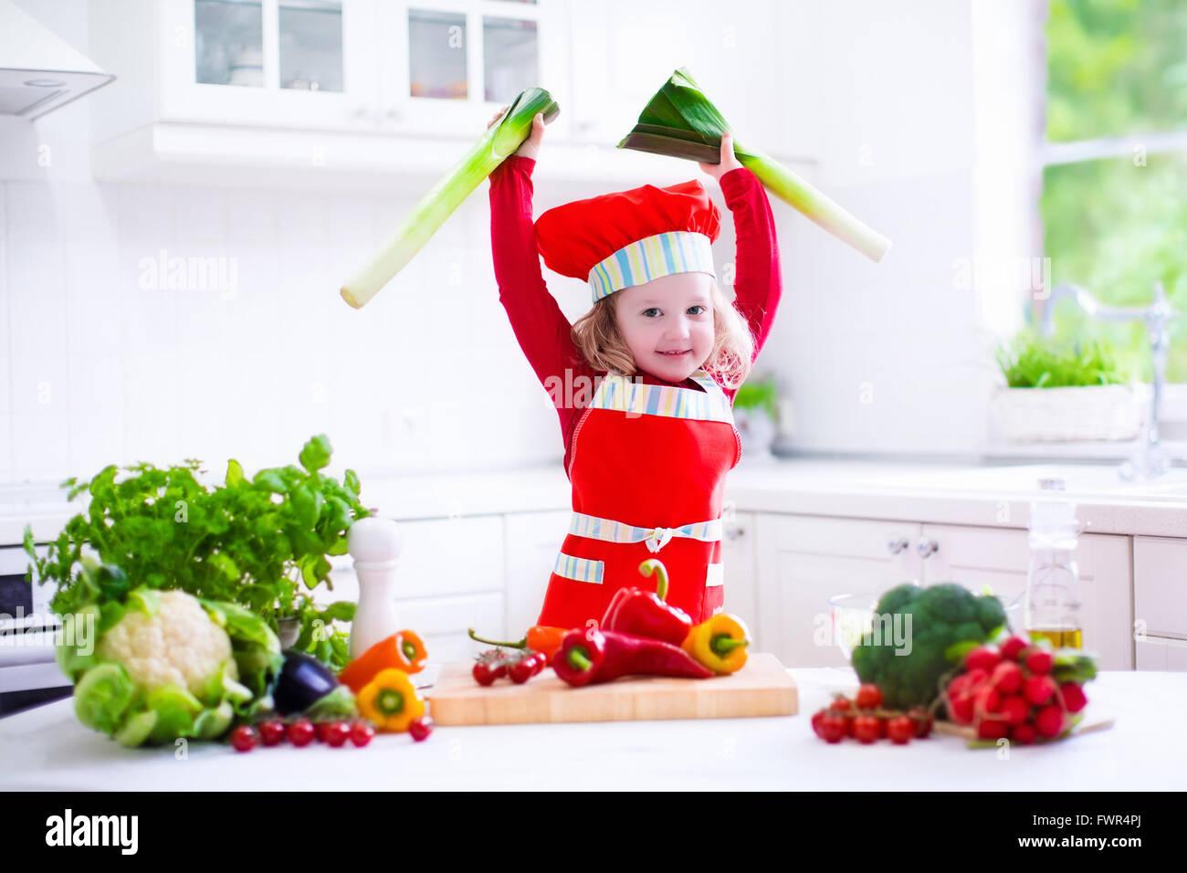 Kids cooking fresh vegetable salad in a white kitchen. Children cook ...