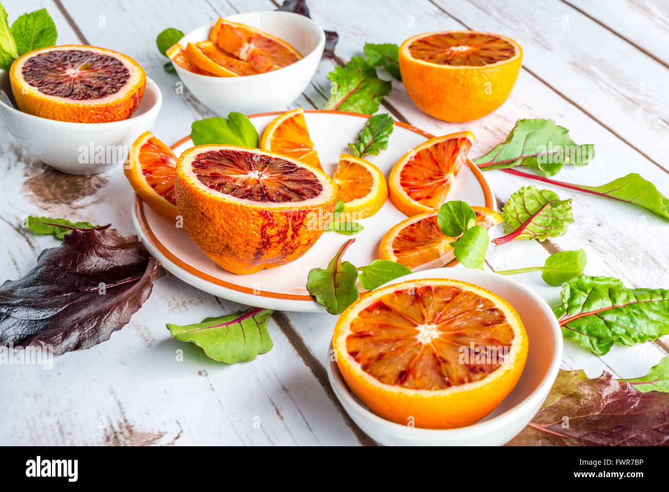 Blood oranges on white plates with green salad leaves - Stock Image