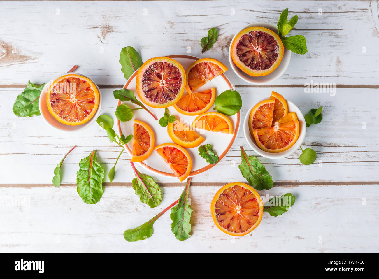 Blood oranges on white plates with green salad leaves on white wood, top view - Stock Image