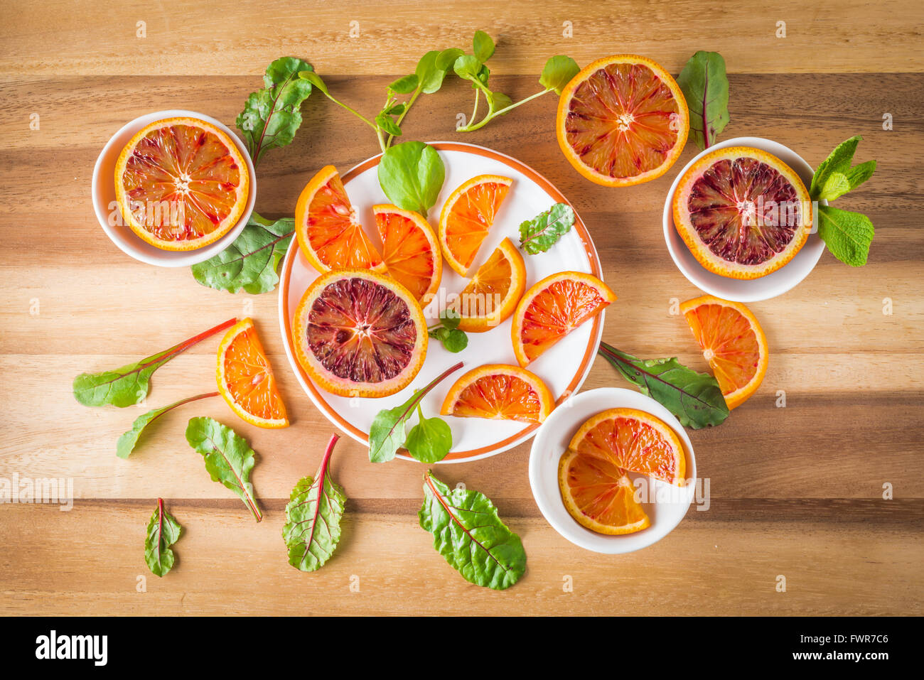 Blood oranges on white plates with green salad leaves on wood, top view - Stock Image
