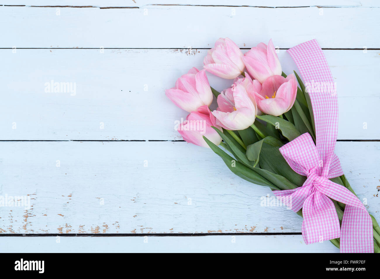 Beautiful bouquet of pink tulips on light wooden background - Stock Image