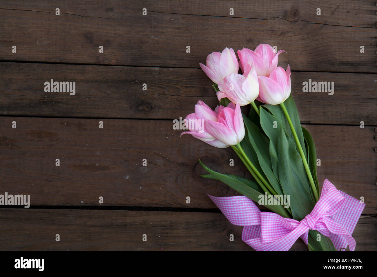 Beautiful bouquet of pink tulips on dark wooden background - Stock Image