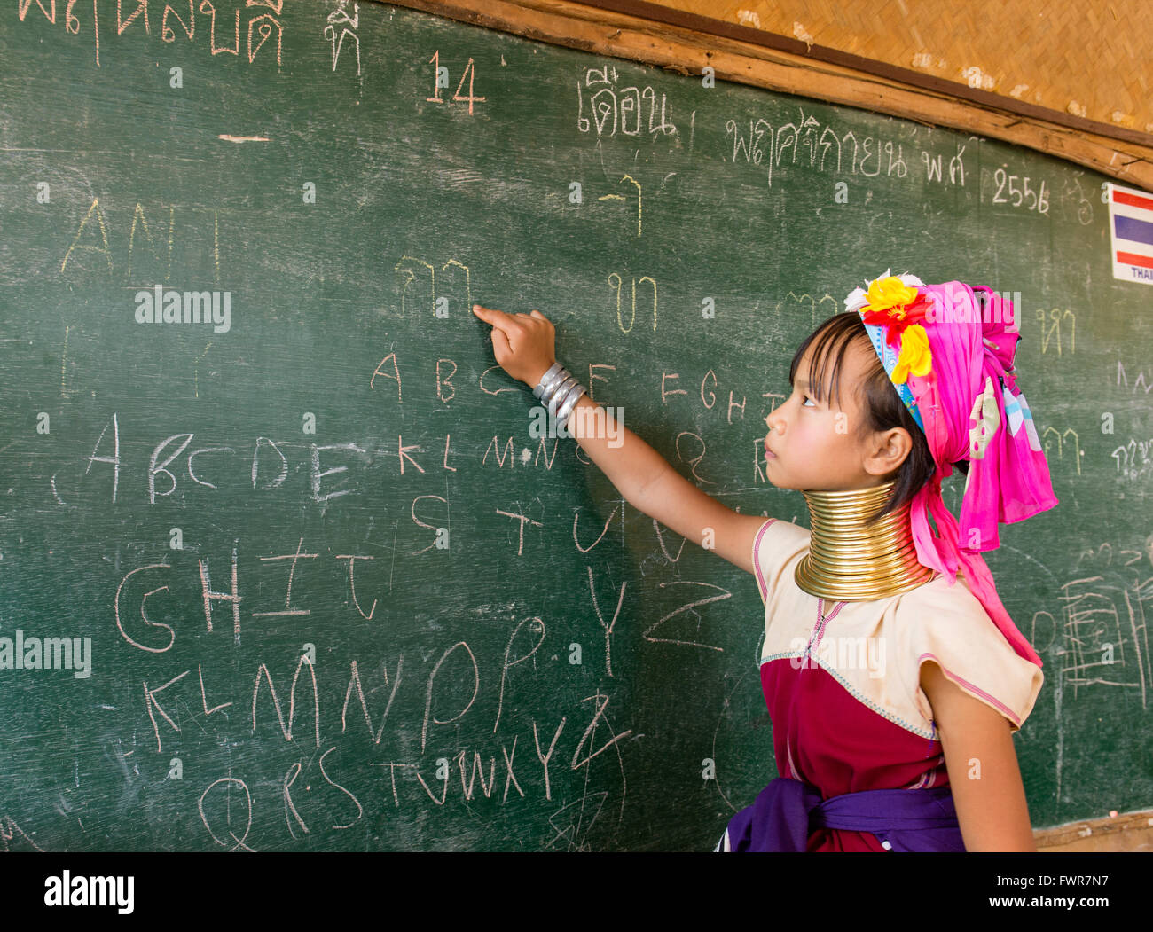 Girl with neck rings at school, Padaung hilltribe, long-necked women, schoolgirl pointing at a blackboard, Chiang - Stock Image