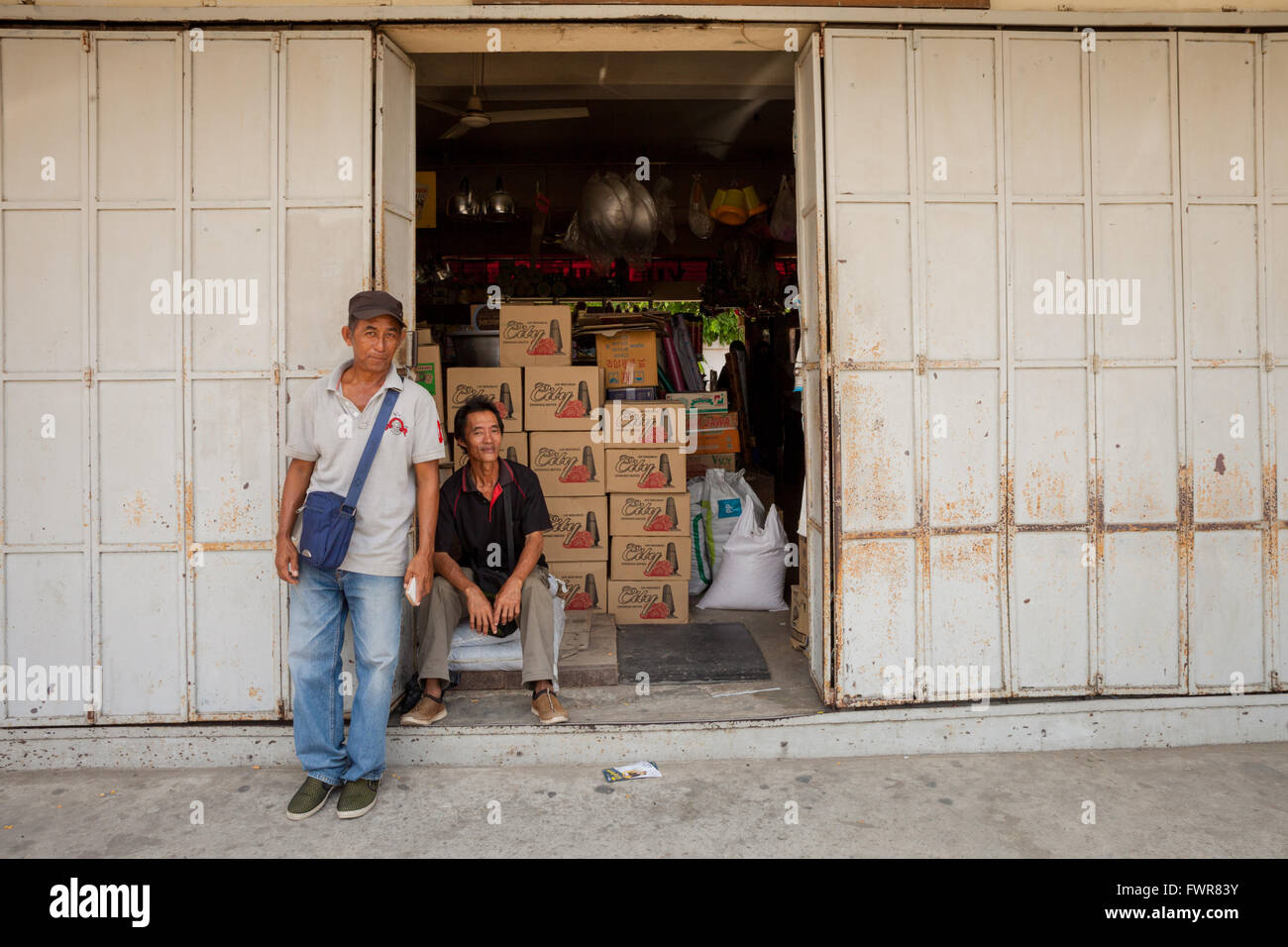 Two men standing by a shop entrance, Kota Marudu, Borneo Malaysia - Stock Image