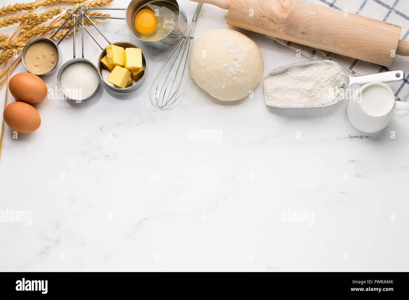 Baking cake, dough recipe ingredients (eggs, flour, milk, butter, sugar) on white table. - Stock Image