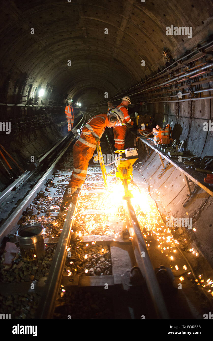 Engineers grinding replacement track components after using thermite welding on London Underground rail track, London, - Stock Image