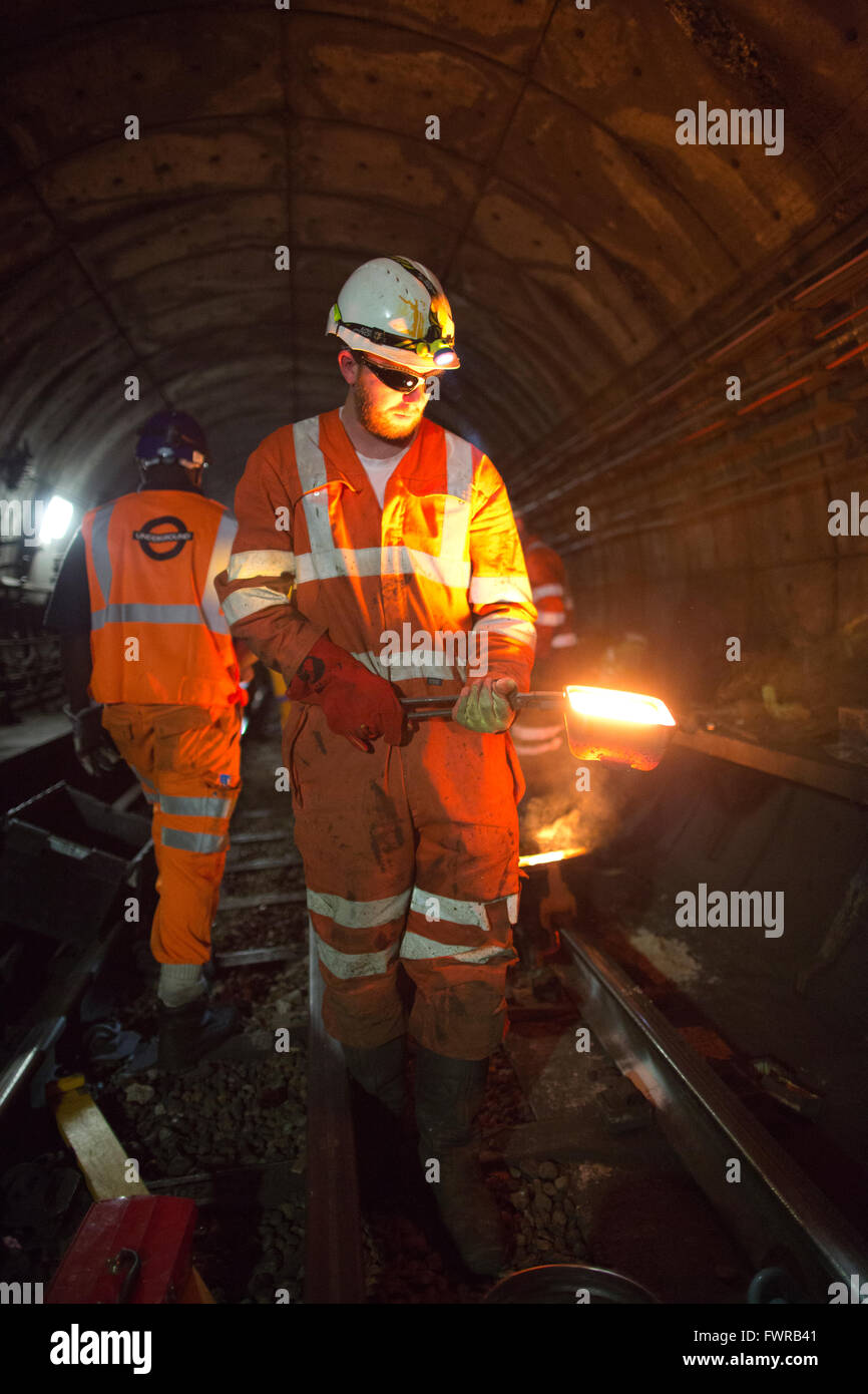 Engineers weld replacement track components together using thermite welding on London Underground rail track, London, - Stock Image