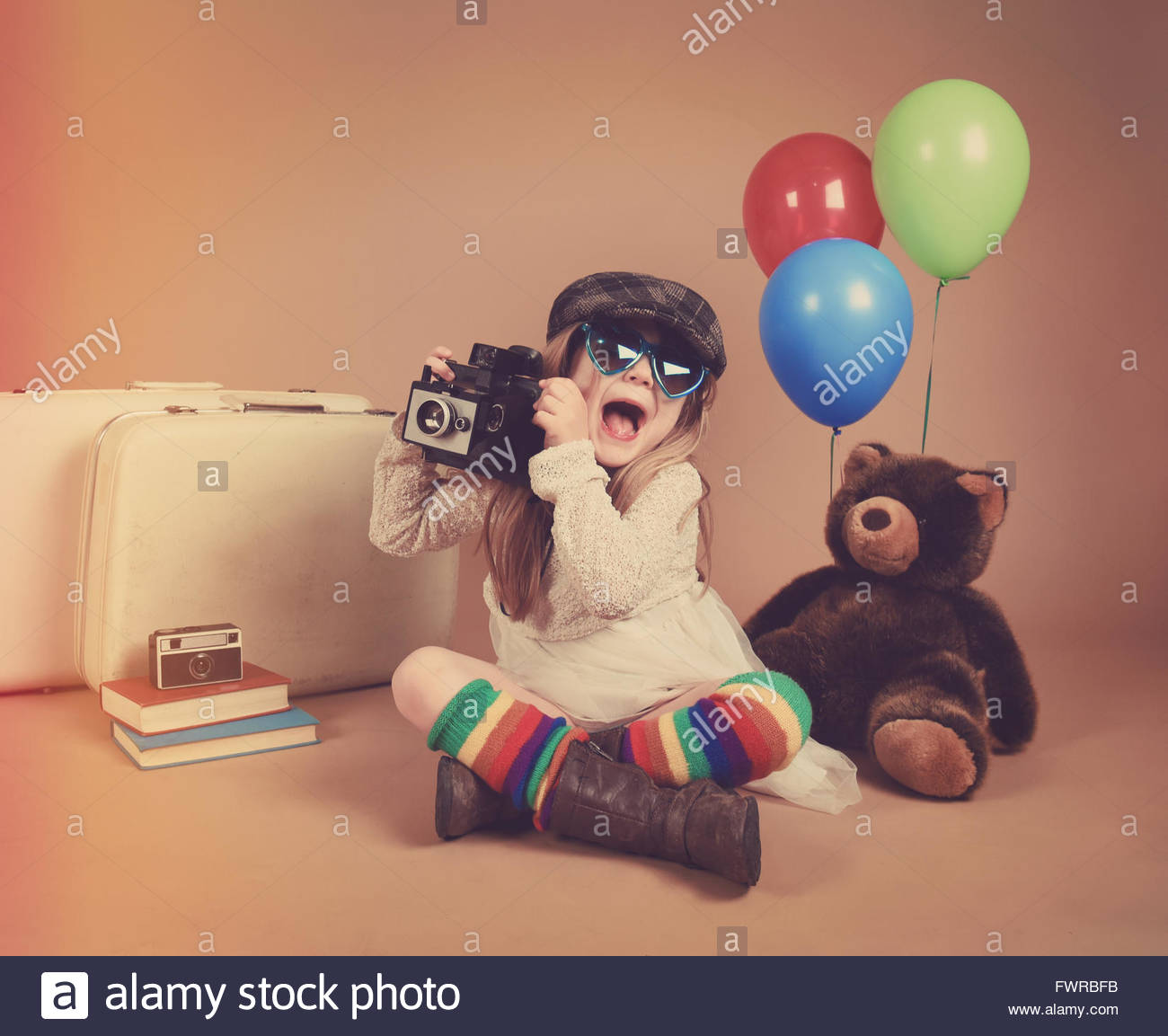 A photo of a vintage child taking a picture with an old camera with balloons and a teddy bear for an art or creative - Stock Image