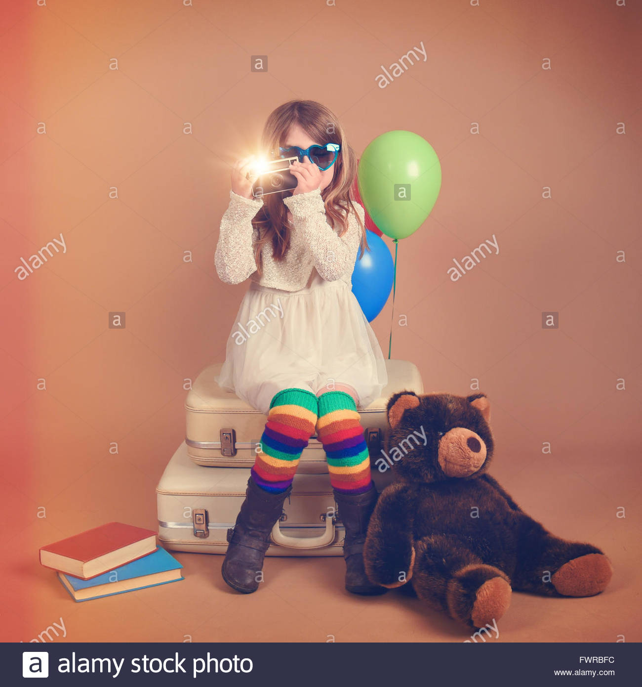 A photo of a vintage child taking a picture with an old camera against with rainbow balloons and a teddy bear for - Stock Image