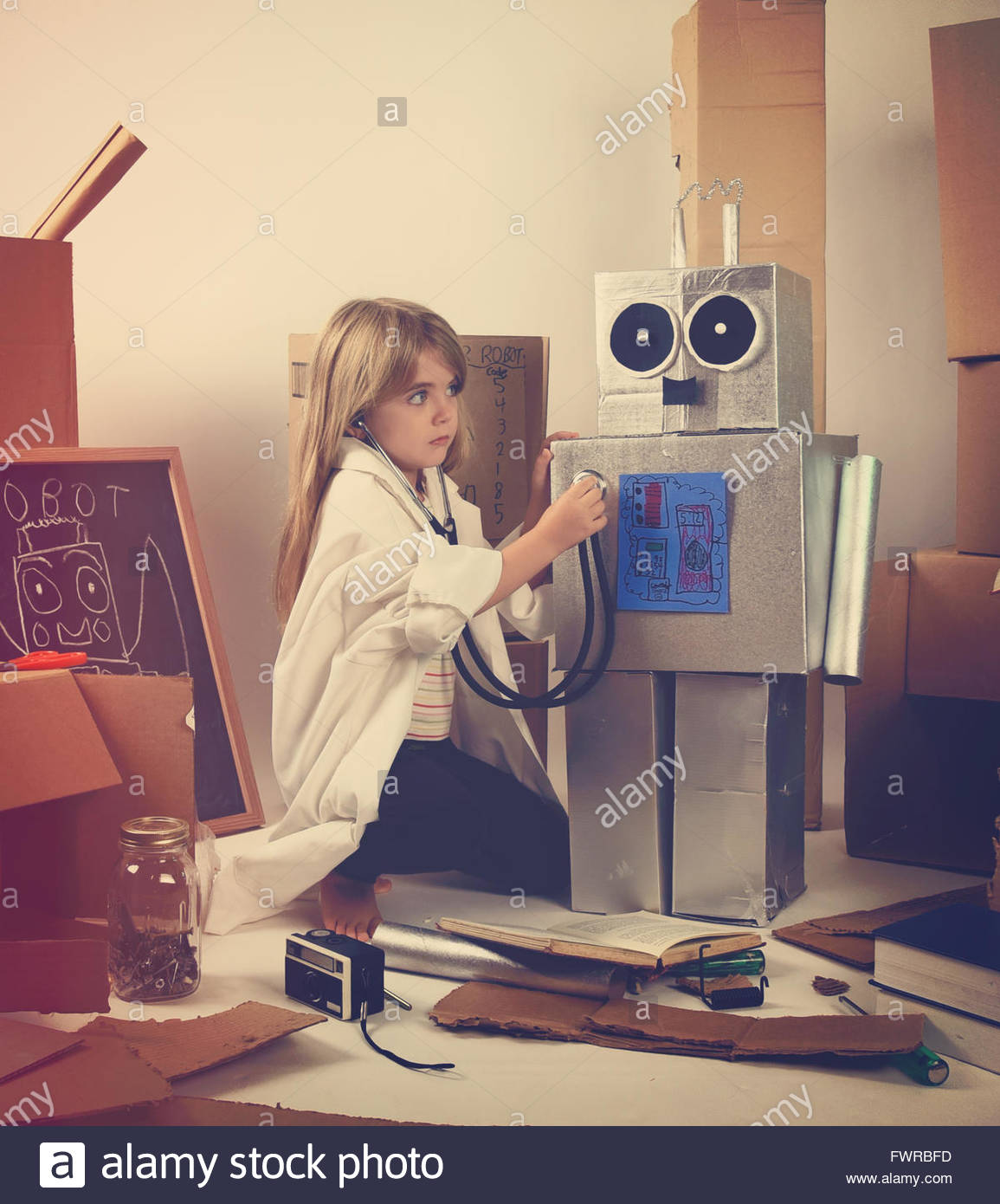 A child science student is inventing a metal robot out of cardboard boxes with tools. The girl is wearing a lab - Stock Image