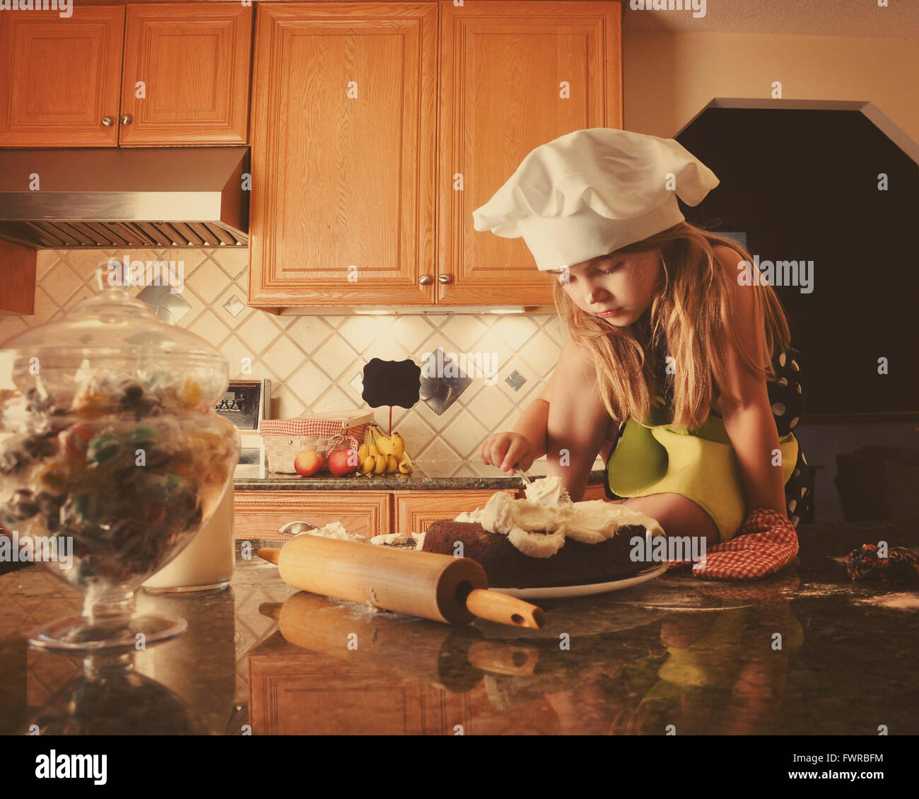 A little child is frosting a cake in the kitchen for a bakery, diet or food concept. The girl is wearing a white - Stock Image