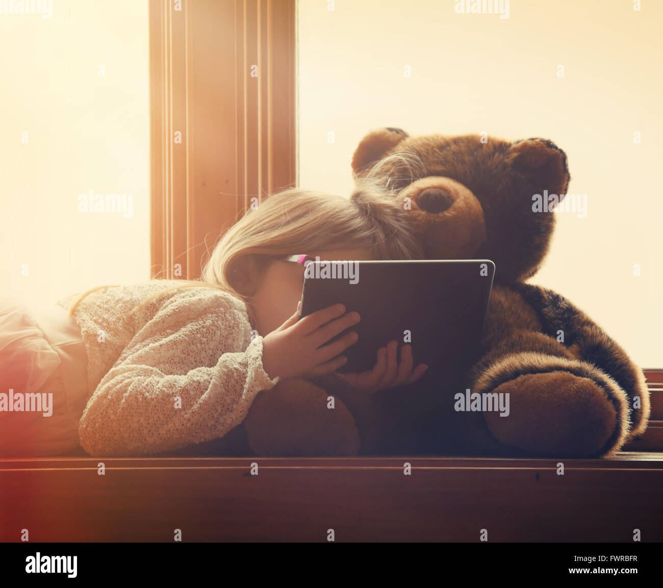 A little girl is holding a technology tablet in a sunny window at home with a teddy bear for an entertainment leisure - Stock Image